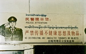 """Police Attention: No distributing any unhealthy thoughts or objects."" A trilingual (Tibetan – Chinese – English) sign above the entrance to a small cafe in Nyalam, Tibet, 1993.""  From wikipedia."