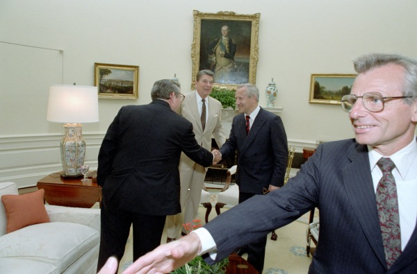 Carlucci reaging out in foreground.  Reagan introduces Baker to Gordievsky.