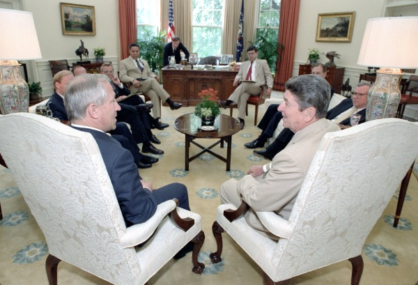 Gordievsky and Reagan in forground.  From left to right: unknown, unknown, Carlucci, Lieutenant General Colin Powell, James Kuhn (?) over desk, Deputy Chief of Staff Ken Duberstein, unknown, and Baker.