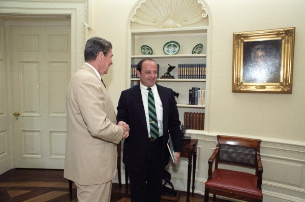 "Reagan meeting an ""unidentified man,"" according to the original caption.  Note the visitors badge."