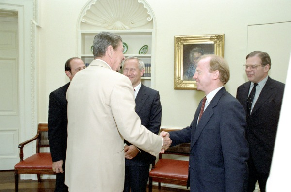 Reagan shaking a second undentified man's hand as Oleg Gordievsky Watches.