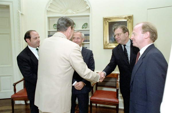 Reagan shakes an unidentified man's hand.  Gordievsky and two other unidentified men look on.