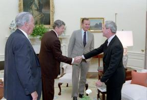 President Reagan, surrounded by White House Chief of Staff Donald Regan and Vice President George H.W. Bush, greets former National Security Advisor Robert McFarlane on his return from Tehran, May 29, 1986. (Photo: Ronald Reagan Library)